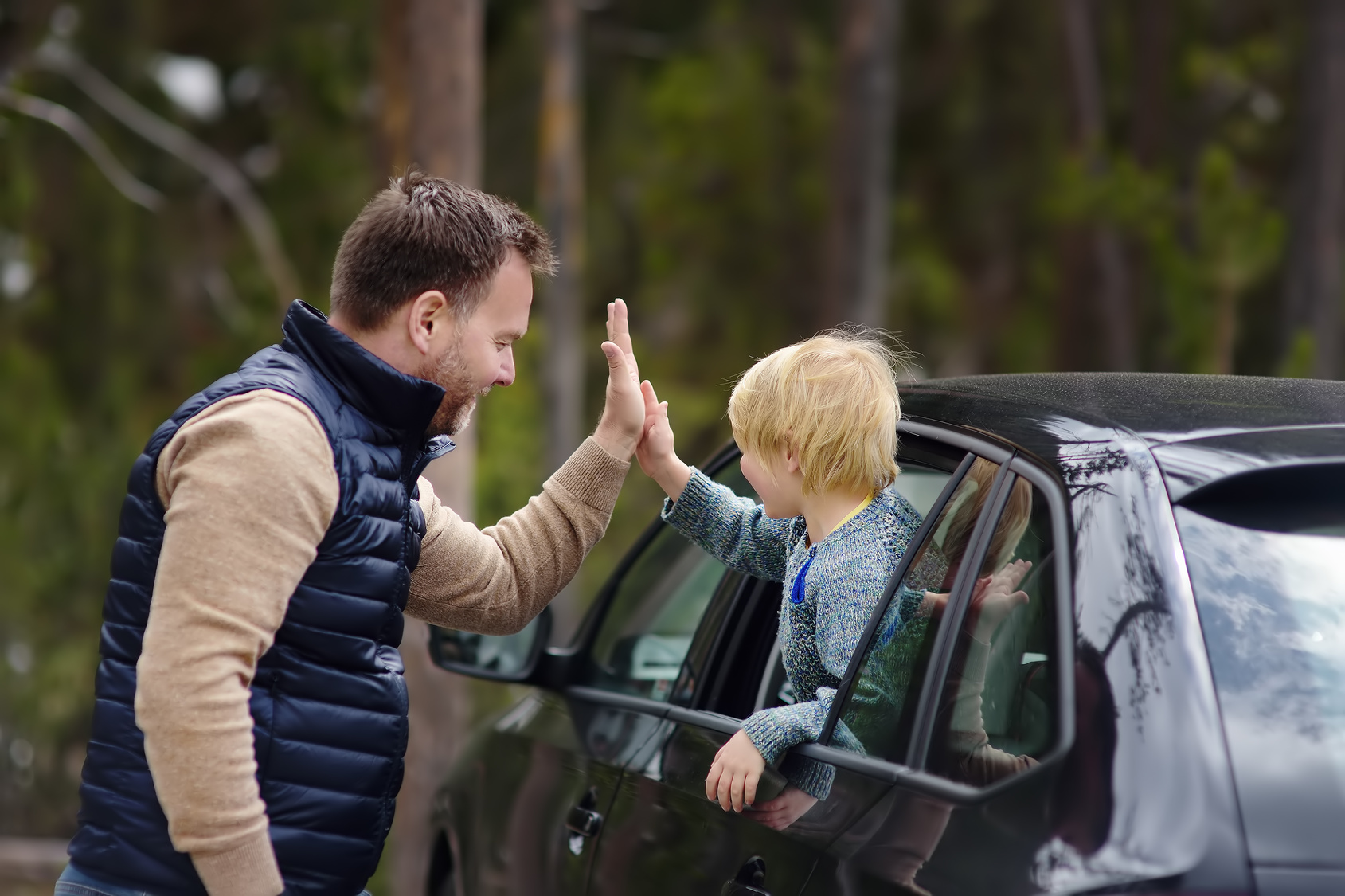 Cute little boy and his father is ready for a trip or a journey by car. They express their delight with a high-five gesture. Quality family time.