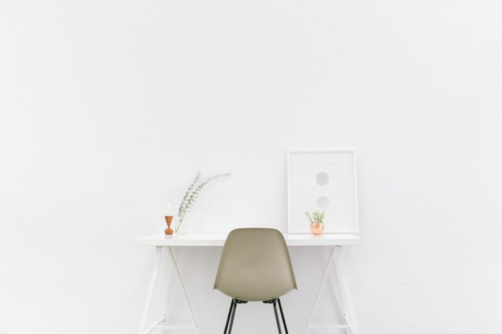 a beige chair and a white table in minimalist home design