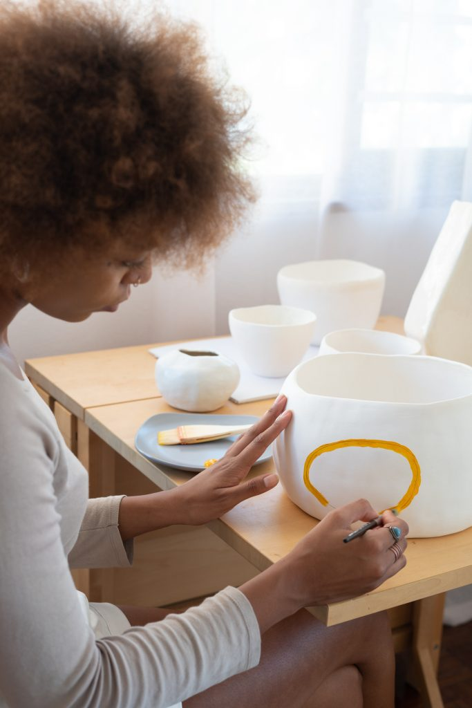 woman painting a vase